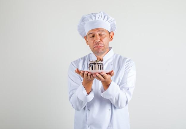 Mannelijke chef-kok in uniform en hoed met cake met gesloten ogen