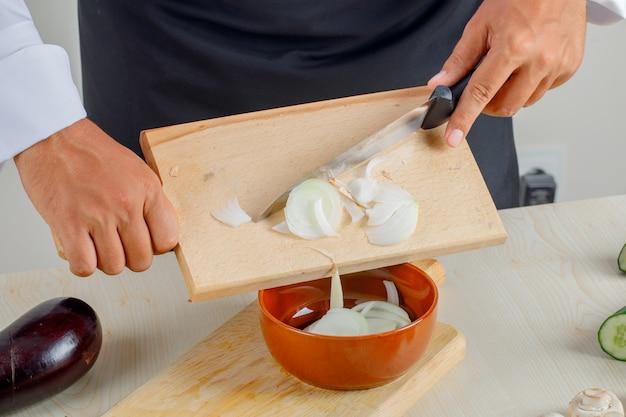 Mannelijke chef-kok in uniform en schort gieten gehakte uien in kom in de keuken