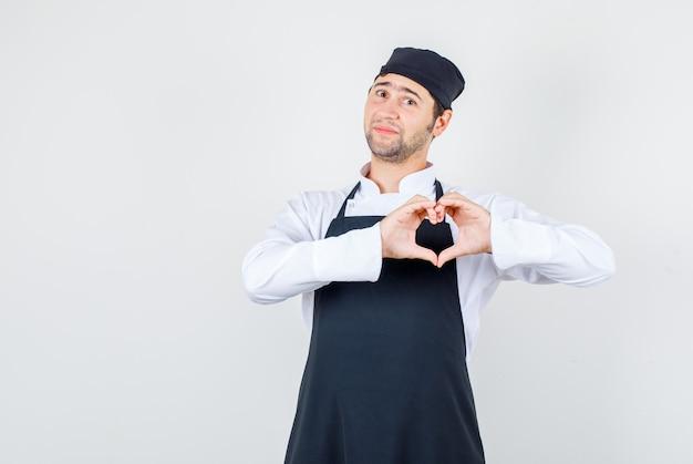 Mannelijke chef-kok in uniform, schort die hartgebaar toont en positief, vooraanzicht kijkt.