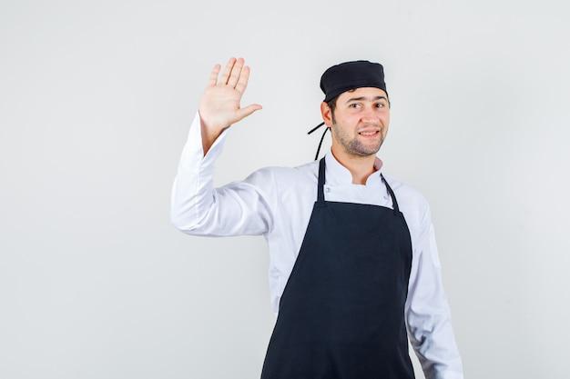 Mannelijke chef-kok in uniform, schort die palm opheft voor begroeting en er blij uitziet, vooraanzicht.