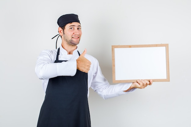 Mannelijke chef-kok in uniform, schort die wit bord met duim omhoog houdt en blij, vooraanzicht kijkt.
