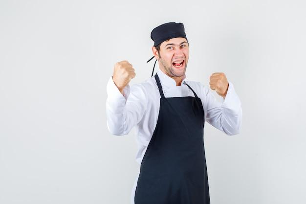 Mannelijke chef-kok in uniform, schort die zich in bokser stelt en energiek kijkt, vooraanzicht.