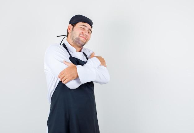 Mannelijke chef-kok in uniform, schort die zichzelf met gesloten ogen knuffelt en er mooi uitziet, vooraanzicht.