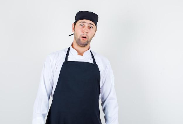 Mannelijke chef-kok in uniform, schort en geschokt, vooraanzicht.