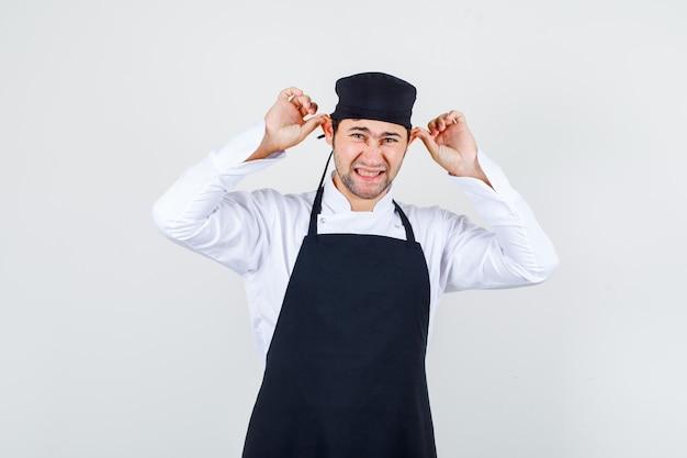 Mannelijke chef-kok in uniform, schort oren trekken, vooraanzicht.