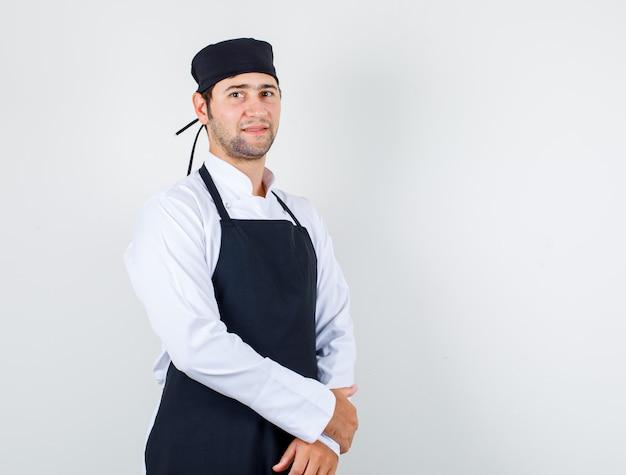 Mannelijke chef-kok in uniform, schort staan en kijken vrolijk, vooraanzicht.