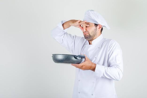 Mannelijke chef-kok in wit uniform die slechte schotel houdt en zijn neus sluit