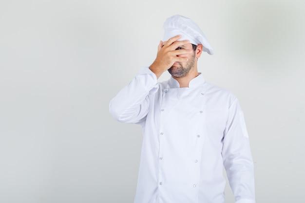 Mannelijke chef-kok in wit uniform kijkt door vingers met één oog en kijkt verlegen