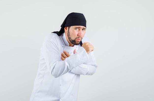 Mannelijke chef-kok in wit uniform lijdt aan keelpijn en hoest en ziet er ziek uit, vooraanzicht.