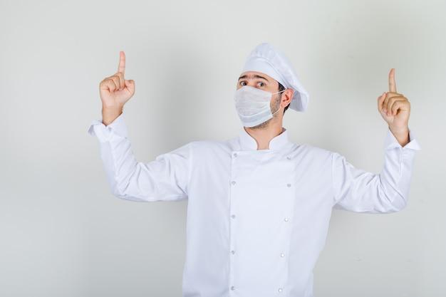 Mannelijke chef-kok in wit uniform, medisch masker vingers omhoog en voorzichtig kijken
