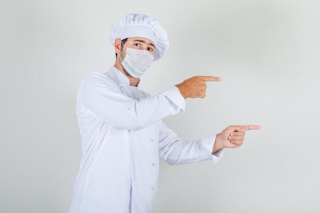 Mannelijke chef-kok in wit uniform, medisch masker wijzende vingers weg en voorzichtig kijken
