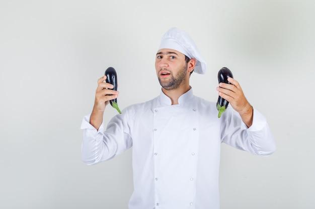 Mannelijke chef-kok in witte uniforme holding aubergine en op zoek positief