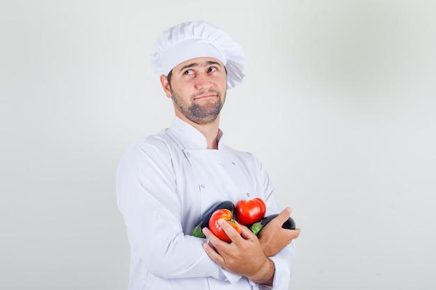 Mannelijke chef-kok in witte uniforme met tomaten en aubergine