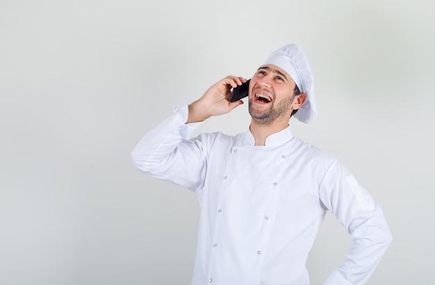 Mannelijke chef-kok lachen tijdens het gesprek aan de telefoon in wit uniform
