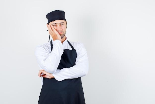 Mannelijke chef-kok leunende wang op opgeheven palm in uniform, schort en peinzend kijken. vooraanzicht.