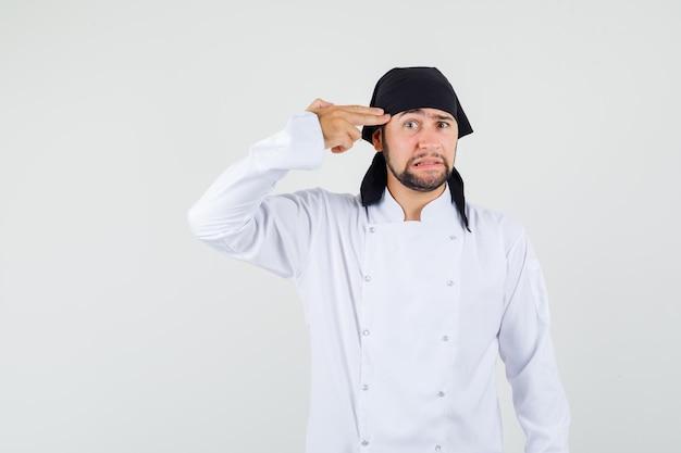 Mannelijke chef-kok maakt zelfmoordgebaar in wit uniform en kijkt angstig. vooraanzicht.