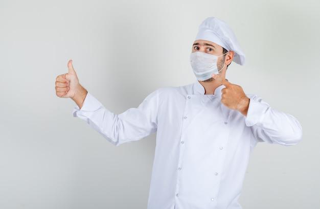 Mannelijke chef-kok medische masker met duim omhoog in wit uniform tonen en voorzichtig kijken