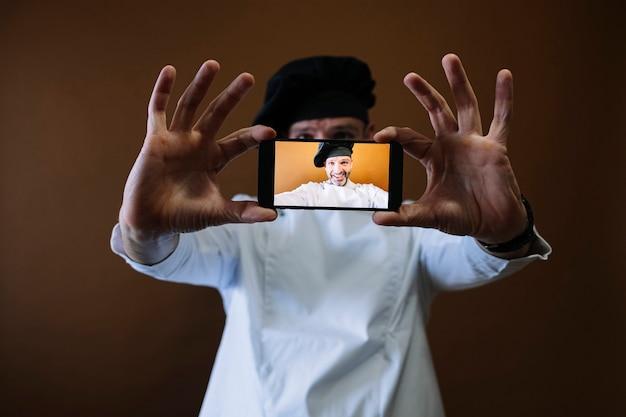 Mannelijke chef-kok met behulp van een telefoon neemt een selfie