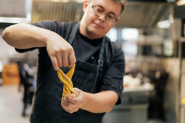 Mannelijke chef-kok met deegwaren