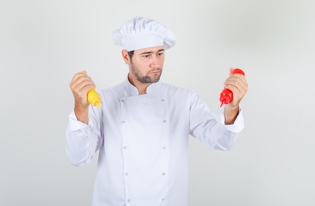 Mannelijke chef-kok met flessen ketchup en mosterd in wit uniform