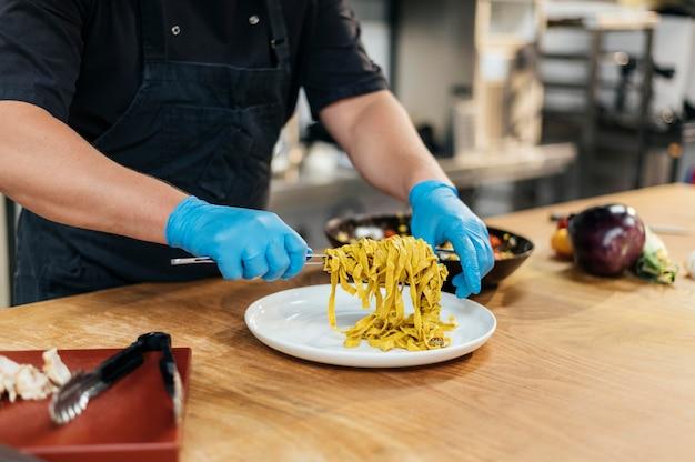 Mannelijke chef-kok met handschoenen pasta op plaat te zetten