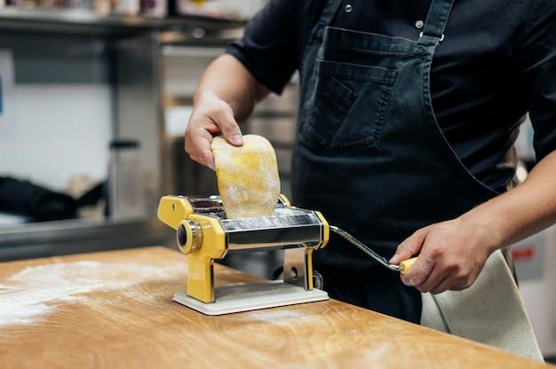 Mannelijke chef-kok met schort rollend deegwaren