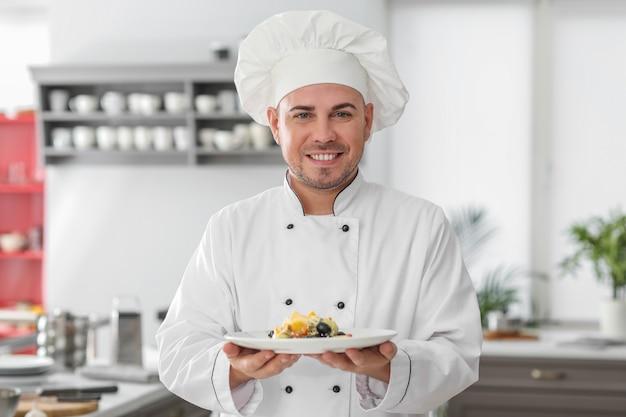 Mannelijke chef-kok met smakelijke salade in keuken