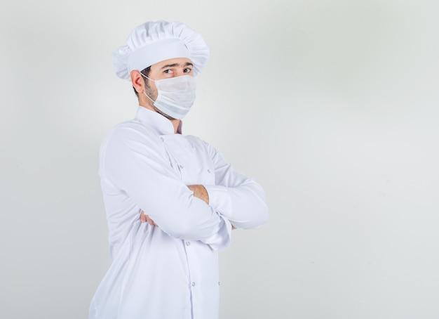Mannelijke chef-kok permanent met gekruiste armen in wit uniform, medisch masker en voorzichtig kijken