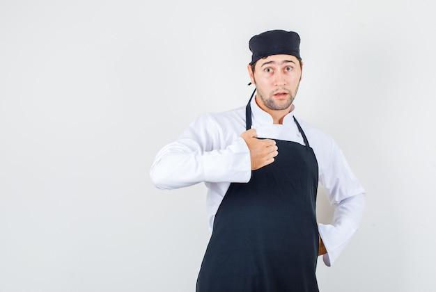Mannelijke chef-kok probeert zijn onschuld in uniform, schort en verbaasd, vooraanzicht te bewijzen.