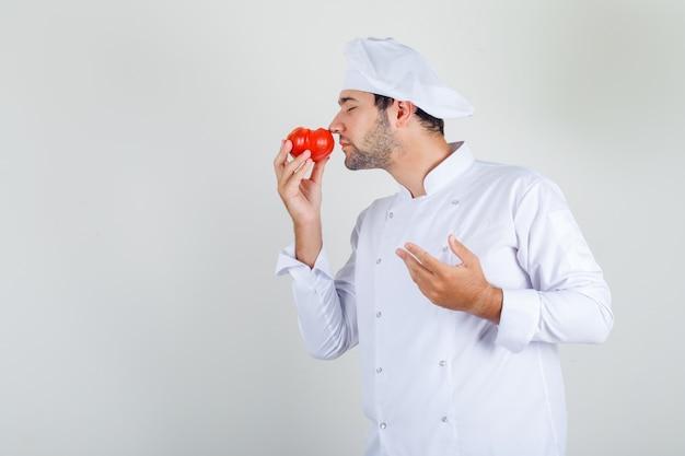 Mannelijke chef-kok ruiken verse tomaat in wit uniform