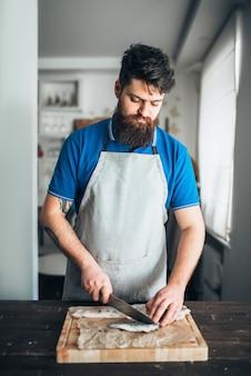 Mannelijke chef-kok snijdt met plakjes mes rauwe vis op houten snijplank. zeevruchten koken. bereiding van verse zeevruchten