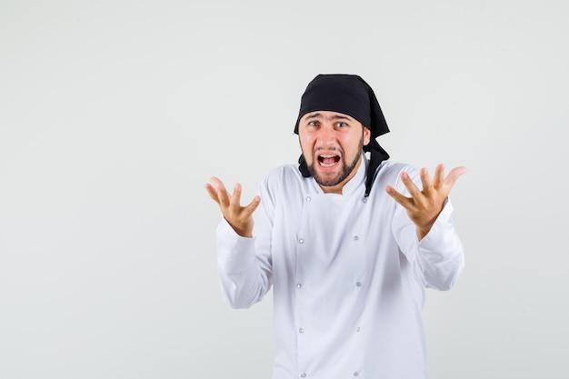 Mannelijke chef-kok steekt zijn handen op in een vragende manier in wit uniform en kijkt geïrriteerd, vooraanzicht.