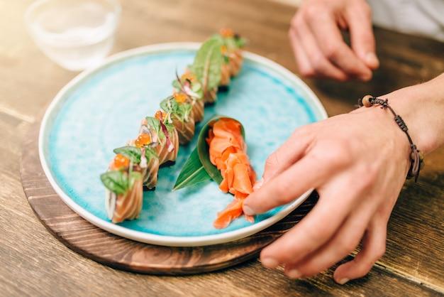 Mannelijke chef-kok sushi rollen, japans eten koken