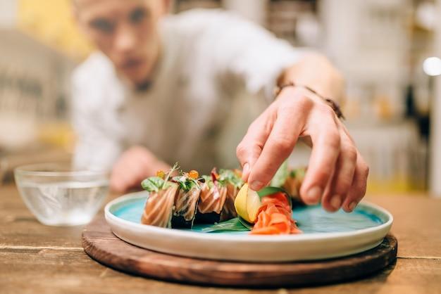 Mannelijke chef-kok sushi rollen, japans voedselbereidingsproces koken