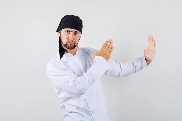 Mannelijke chef-kok toont karate chop gebaar in wit uniform en ziet er zelfverzekerd uit. vooraanzicht.