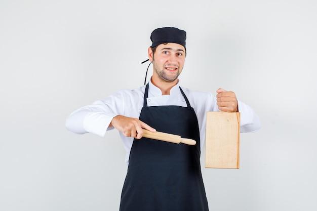 Mannelijke chef-kok wijzende deegroller op snijplank in uniform, schort en op zoek vrolijk, vooraanzicht.