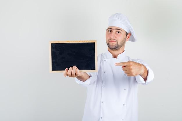 Mannelijke chef-kok wijzende vinger op bord in wit uniform en op zoek vrolijk.