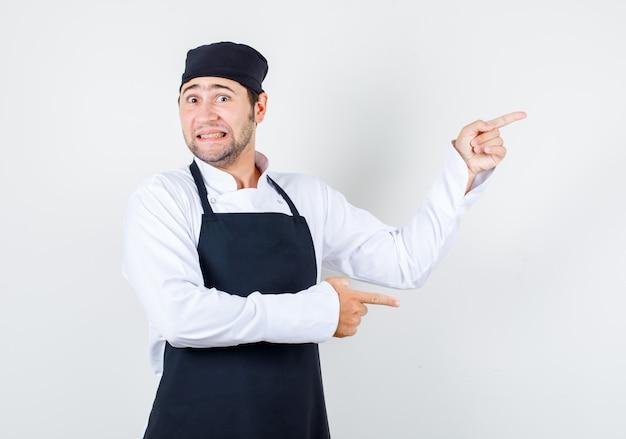 Mannelijke chef-kok wijzende vingers naar de zijkant in uniform, schort en bang, vooraanzicht op zoek.