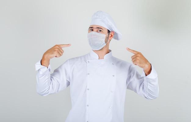 Mannelijke chef-kok wijzende vingers op medisch masker in wit uniform en voorzichtig kijken