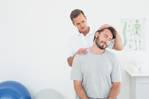Mannelijke chiropractor die halsaanpassing doet