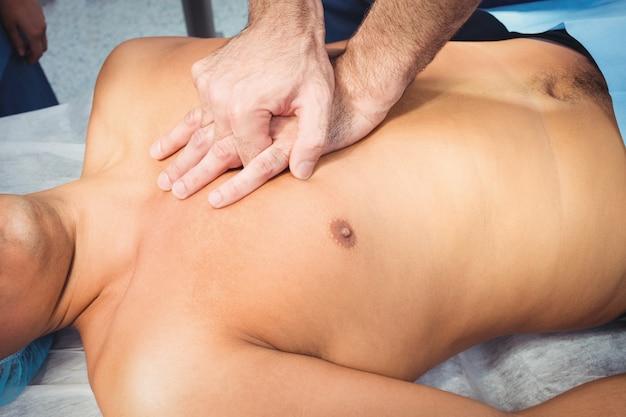 Mannelijke chirurg die cardiopulmonale reanimatie uitvoert bij een bewusteloze patiënt