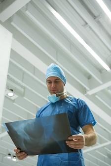 Mannelijke chirurg die x-ray onderzoekt