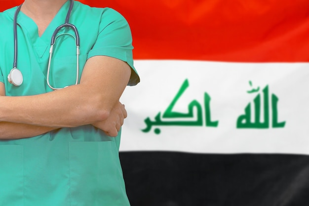 Mannelijke chirurg of arts met een stethoscoop op de achtergrond van de vlag van irak