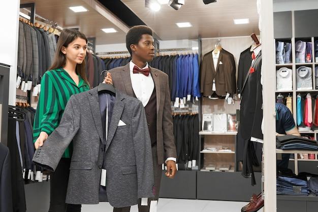 Mannelijke cliënt die modieus kostuum in winkel kiezen.