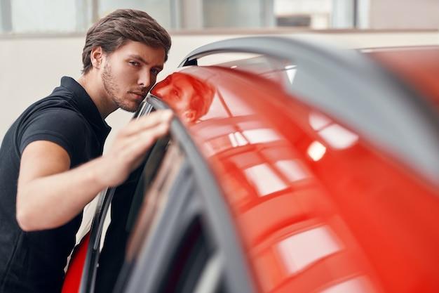 Mannelijke cliënt verf op voertuig controleren