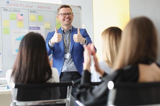 Mannelijke coach die ok teken toont voor juichende luisteraars