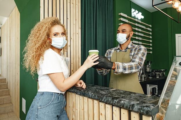 Mannelijke coffeeshopmedewerker die klaar bevel geeft aan de cliënt die gezichtsmasker draagt