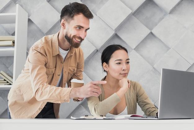 Mannelijke collega die op laptop richt