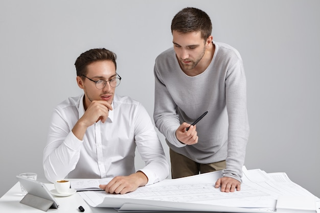 Mannelijke collega's die papierwerk doen