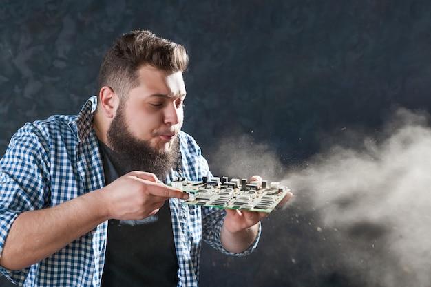 Mannelijke computeringenieur blaast het stof van het moederbord. elektronische apparaten die technologie en serviceondersteuning repareren